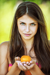 beautiful woman holding tangerine