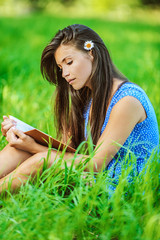 woman sitting on grass and reading book