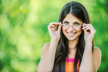 young beautiful woman adjusts glasses