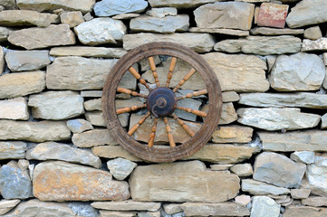 Vintage Spinning Wheel on Stone Wall