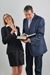 Beautiful business woman with male colleague reading a book