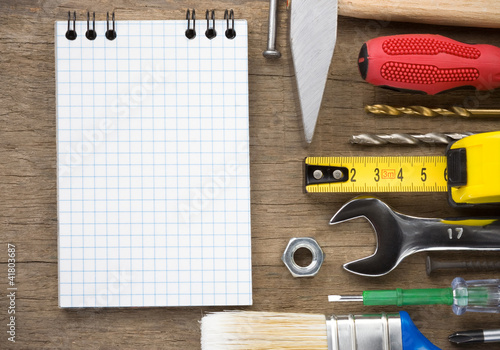 set of tools and notebook on wood
