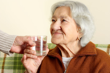 Grandmother drinks a glass water
