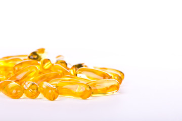 Capsules of fish oil and vitamins on white background.