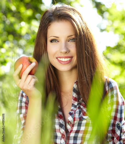 Woman with apple in garden