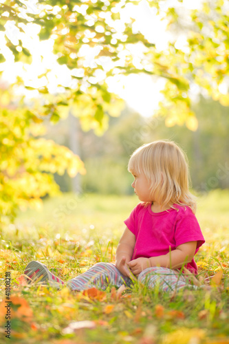 Adorable baby sit on grass with leaf under trees shadow on sunse