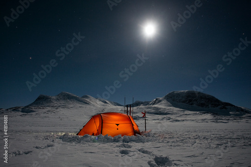 canvas print picture Moon over a illuminated Tent on a Winter Expedition