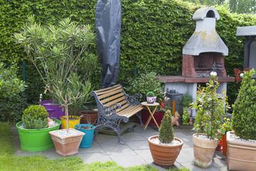 Gartenterrasse mit  Grill und gemütlicher Gartenbank