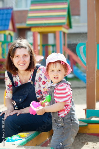 happy mother with  toddler  in sandbox
