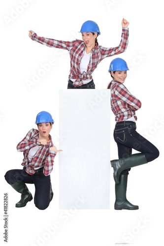 Triplets dancing around a blank sign