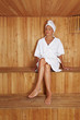 Ältere Frau sitzt in Sauna