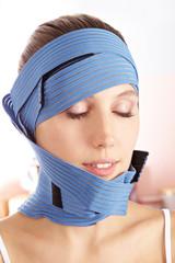 Frau mit Bandage nach Schönheitsoperation