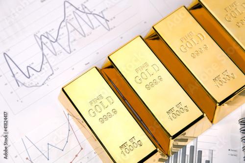 Photo of gold bars on graphs and statistics, studio shots - 41824417