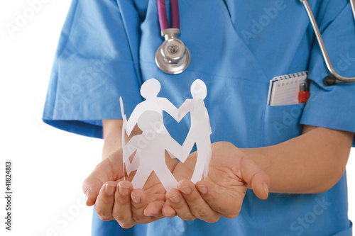 A female doctor holding paper people, focus on the hands