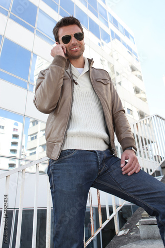 Fashionable man standing outdoors on phone