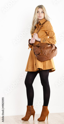 standing woman wearing coat and fashionable brown shoes with a h