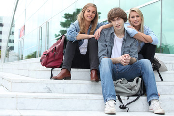 Three students sitting outside on some steps