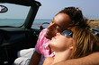 Couple relaxing in a convertible car