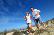 Couple having fun runnning down sand dune