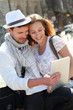 Couple in town using electronic tablet