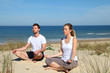 Couple doing yoga exercices on a sandy beach