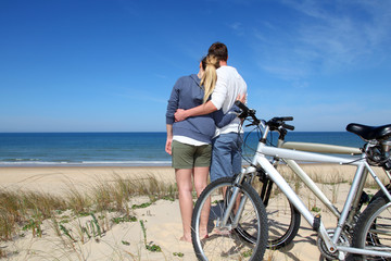 Couple standing on a sand dune with bicycles