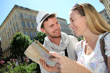 Couple of tourists looking at city tour map