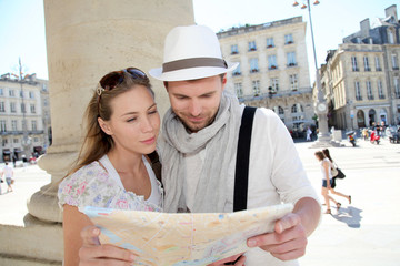 Couple holding a touristic map of Bordeaux