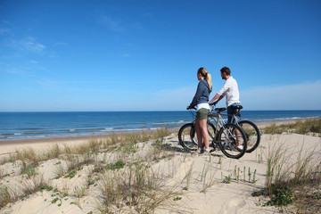 Couple with bicycles looking at the ocean