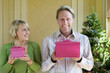 Mature couple holding pink gift boxes by Christmas tree, woman with small gift box looking at man, smiling