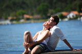 Couple relaxing on a lake bridge in summertime