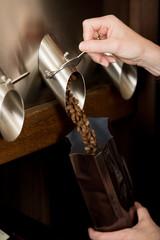 verkäuferin füllt kaffeebohnen in eine tüte