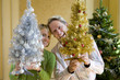 Couple by Christmas tree with small ornamental trees, smiling, portrait