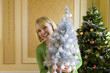 Woman by Christmas tree with small ornamental tree, smiling, portrait