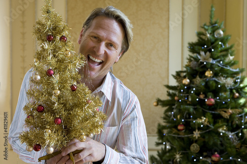 Mature man by Christmas tree with small ornamental tree, smiling, portrait