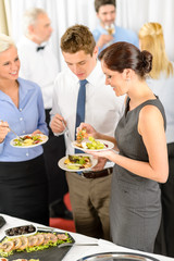 Business colleagues eat buffet appetizers