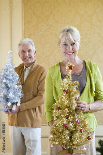 Senior couple with ornamental Christmas trees, smiling, portrait, close-up of woman