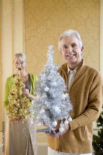 Senior couple with ornamental Christmas trees, smiling, portrait, close-up of man