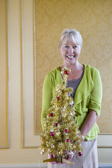 Senior woman with ornamental Christmas tree, smiling, portrait