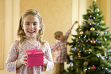 Portrait of girl (4-6) with pink gift box, brother (7-9) hanging decoration on Christmas tree in background