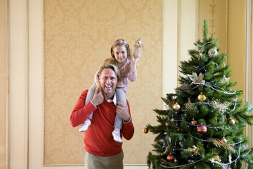 Girl (4-6) with angel decoration on father's shoulders by Christmas tree, smiling, portrait