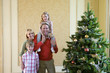 Family of four by Christmas tree, girl (4-6) on father's shoulders, smiling, portrait