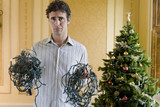 Young man with tangled bunches of Christmas lights by Christmas tree, portrait