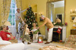 Family around Christmas tree, father decorating tree, grandfather giving gift to girl (5-7)