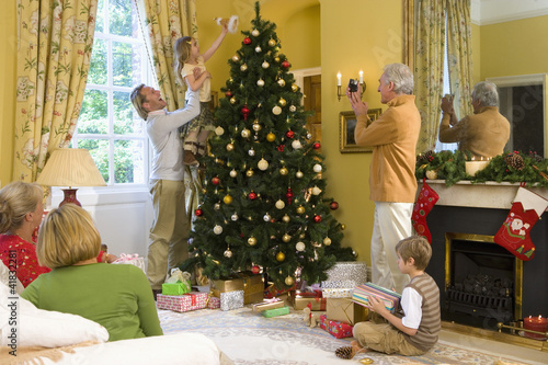 Family by Christmas tree, grandfather taking photograph of girl (5-7) putting angel decoration on tree