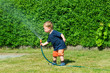 Kleinkind mit Gartenschlauch