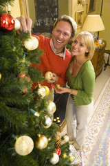 Couple decorating Christmas tree, smiling, elevated view