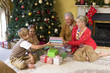 Family of four giving gifts by Chirstmas tree