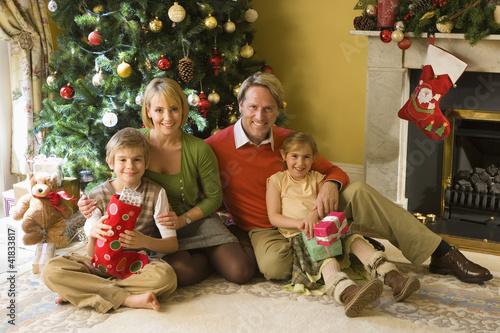 Family of four by Christmas tree with gifts, portrait