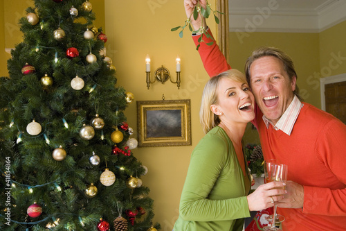 Couple by Christmas tree with champagne flutes, man holding up mistletoe, portrait